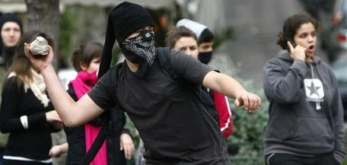 1-a-youth-throws-stones-at-police-during-a-rally-in-central-athens_334