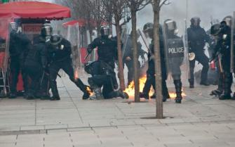 Kosovo police member try to extinguish fire from molotov cocktails thrown by supporters of the opposition during a violent clashes in Kosovo capital Pristina on Saturday, Jan. 9, 2016. A government building was set on fire in Pristina on Saturday as supporters of Kosovo's main opposition parties gathered during a rally organised as part of their continued attempts to bring down the government. Security forces used tear gas to push back protesters. (AP Photo/Visar Kryeziu)