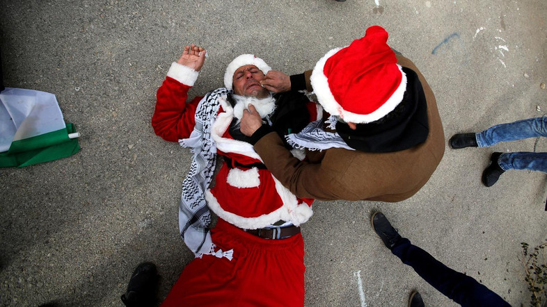 A man tends to a Palestinian protester, dressed as Santa Claus, after inhaling tear gas fired by Israeli troops during clashes in the West Bank city of Bethlehem, December 23, 2016. REUTERS/Mussa Qawasma     TPX IMAGES OF THE DAY - RTX2WALS