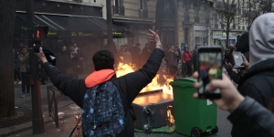 "A young man gestures in front of burning dustbins which obstruct the street, during a protest of students against police brutality, following the alleged rape of Theo, next to the ""Lycee Voltaire"" secondary school in Paris, on February 23, 2017. / AFP PHOTO / GEOFFROY VAN DER HASSELT"