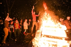 A fans sprays beer on the crowd while standing on a burning couch. Thousands gathered around a couch fire on 19th Avenue Northeast and Northeast 47th Street on Sunday night to celebrate the Seahawks' first Super Bowl win.